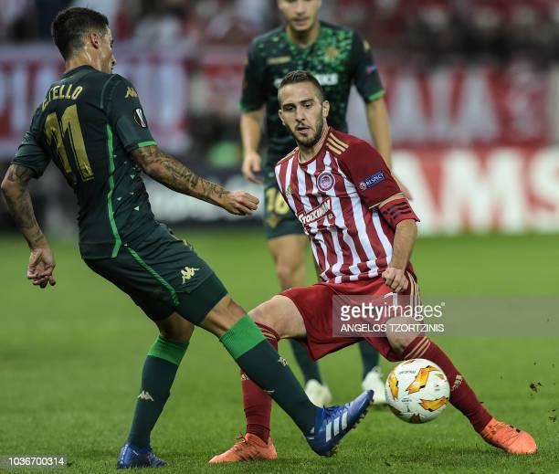 Olympiakos' Greek midfielder Kostas Fortounis fights for the ball with Real Betis' Spanish forward Cristian Tello during the UEFA Europa League Group...