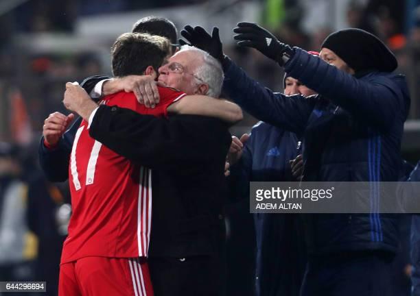 Olympiakos' Iranian forward Karim Ansarifard celebrates with staff members after scoring a goal during the UEFA Europa League round of 32 second leg...