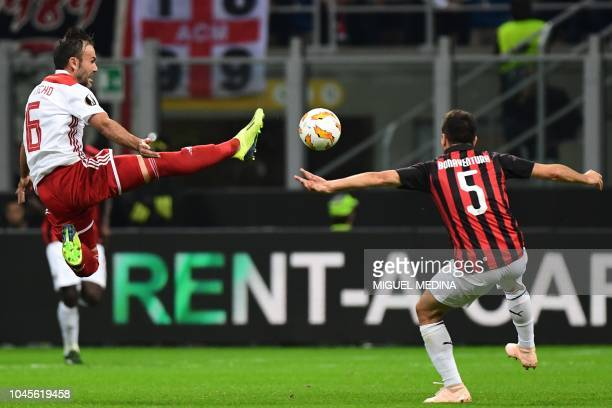 Olympiakos' Israeli midfielder Bebars Natcho jumps for the ball next to AC Milan's Italian midfielder Giacomo Bonaventura during the Europa League...