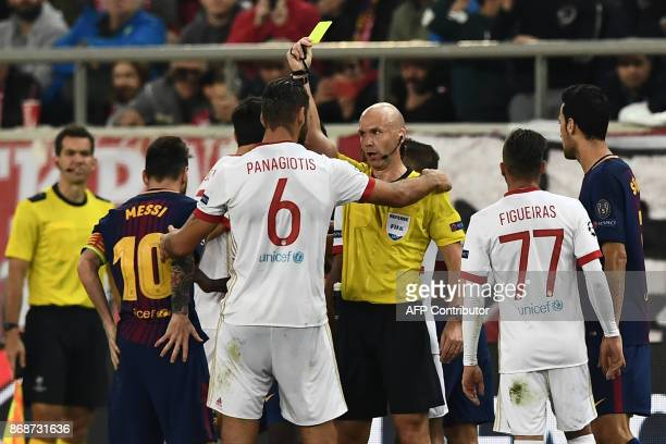Olympiakos' midfielder Panagiotis Tachtsidis receives a yellow card by British referee Anthony Taylor during the UEFA Champions League group D...
