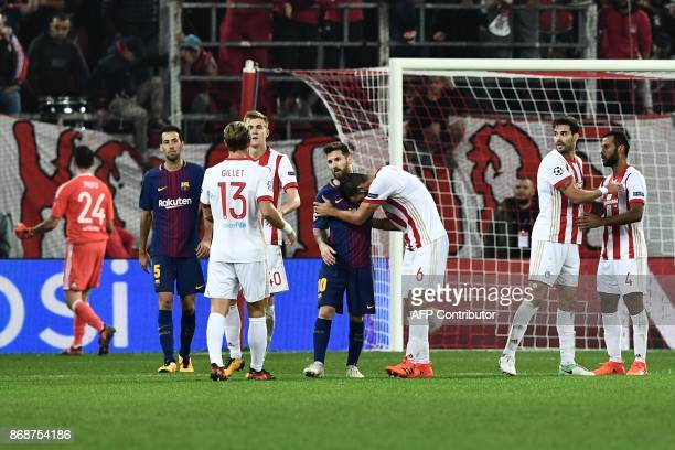 Olympiakos' midfielder Panagiotis Tachtsidis shakes hands with Barcelona's Argentinian forward Lionel Messi at the end of the UEFA Champions League...