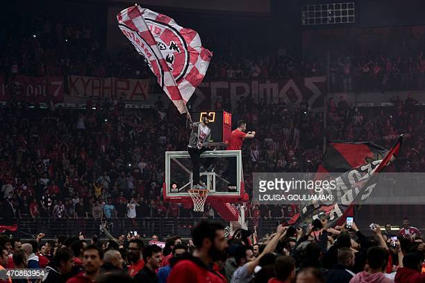 Olympiakos Piraeus fans celebrate with players after their win over Barcelona during their play off Euroleague basketball match at the Peace and...