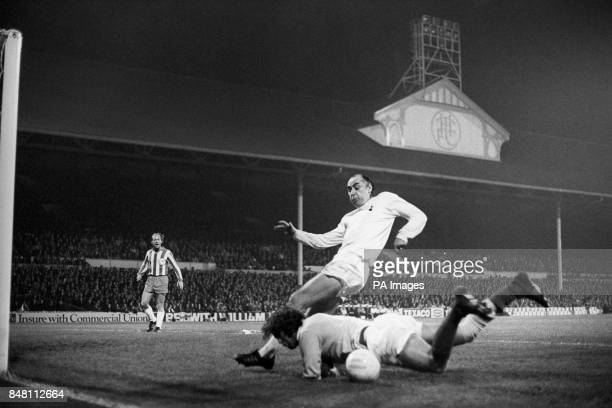 Olympiakos Piraeus goalkeeper Panagiotis Kelessidias dives at the feet of Tottenham Hotspur's Alan Gilzean
