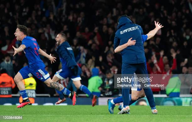 Olympiakos players and staff react to their win over Arsenal during the UEFA Europa League round of 32 second leg match between Arsenal FC and...