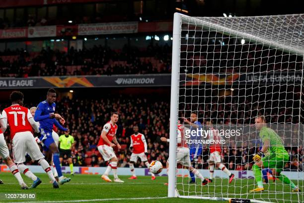 Olympiakos' Senegalese defender Cisse Abdou watches his header beat Arsenal's German goalkeeper Bernd Leno for the opening goal of the UEFA Europa...