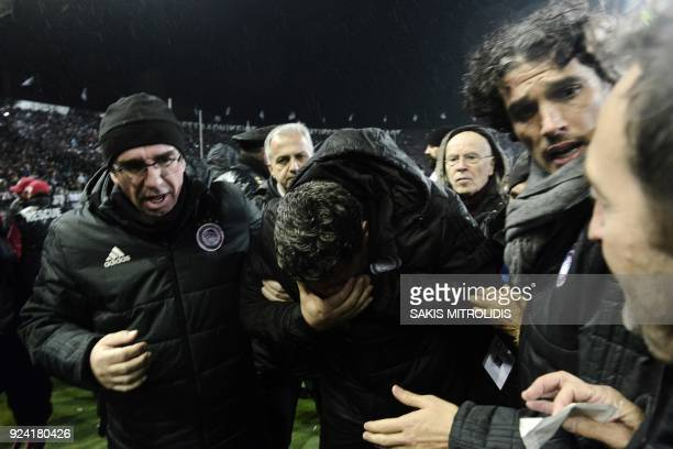 Olympiakos' Spanish coach Oscar Garcia Junyent reacts after being hit in the face by a toilet roll thrown by a Paok fan prior to the Greek...