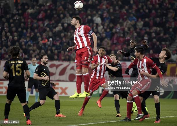 Olympiakos' Spanish defender Alberto Botia heads the ball during the UEFA Europa League round of 32 first leg football match between Olympiakos and...