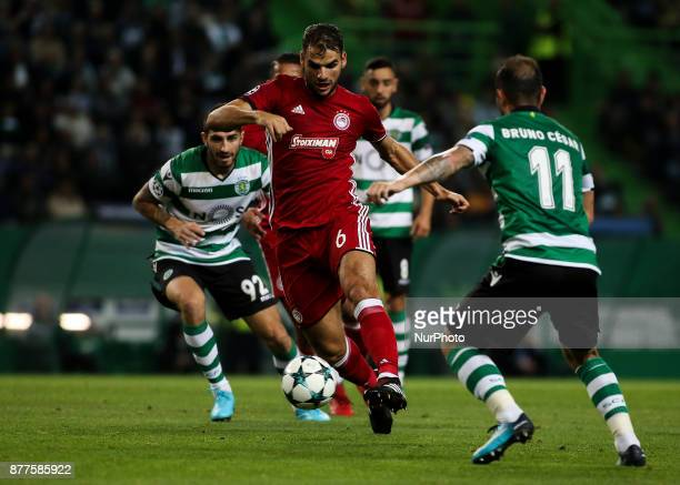 Olympiakos's midfielder Panagiotis Tachtsidis vies with Sporting's forward Bruno Cesar during the Champions League football match between Sporting CP...