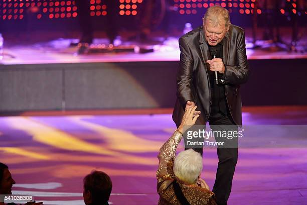 Olympian Dawn Fraser shakes hands with John Farnham as he performs during the Prime Minister's Olympic Dinner at The Melbourne Convention and...