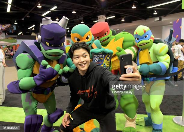 Olympian Ice Dancer Alex Shibutani poses with Nickelodeon's 'Rise of the Teenage Mutant Turtles' costumed characters at Nickelodeon's booth at 2018...