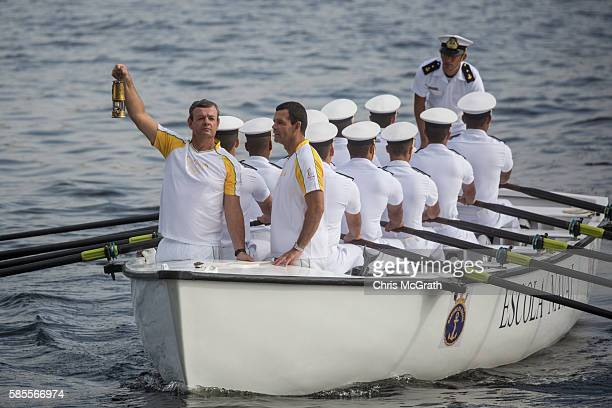 Olympian Lars Grael carries the Olympic flame aboard a Brazilian Naval Academy boat during the Olympic Torch relay ahead of the Rio 2016 Olympic...