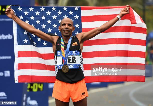 Olympian Meb Keflezighi of the US holds up the national flag after crossing the finish line in Men's Division during the 2017 TCS New York City...