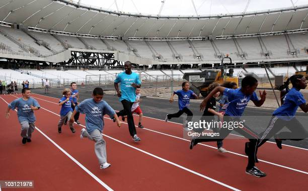Olympian Michael Johnson races with local kids inside the Olympic Stadium during a visit to the Olympic Park to mark 'two years to go' to London 2012...
