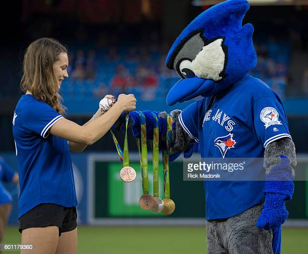 Olympian Penny Oleksiak hands over her medals to Ace prior to throwing the ceremonial first pitch Toronto Blue Jays V Boston Red Sox in regular...