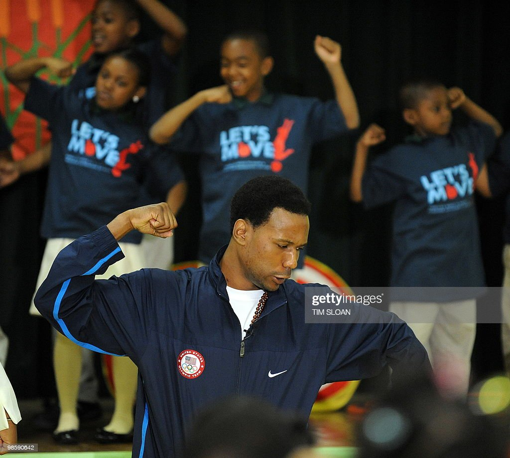 Olympian speedskater Shani Davis shows kids an exercise during an event highlighting physical activity as a critical element of US Frist Lady Michelle Obama's 'Let's Move' initiative on April 21, 2010 in the North East section of Washington, DC. AFP PHOTO / Tim Sloan