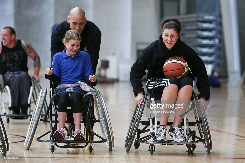 Olympic Ambassador Paora Winitana (L) pushes a child during a game of wheelchair basketball at the launch of the New Zealand Olympic Ambassador Programme at ASB Sports Centre on June 20, 2013 in Wellington, New Zealand.