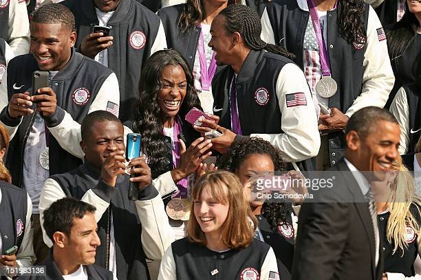 S Olympic and Paralympic team members including gold medal runner Dee Dee Trotter react to the arrival of US President Barack Obama during an event...