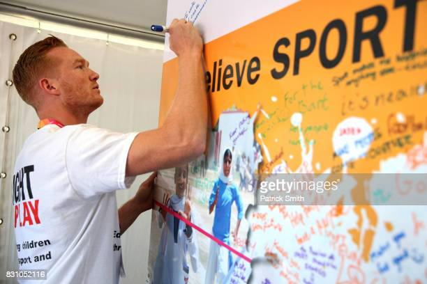 Olympic and World Champion Long Jumper Greg Rutherford writes a message as he attends a Right To Play event during day ten of the 16th IAAF World...