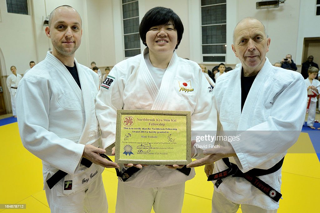 Olympic and World champion, Maki Tsukada of Japan, gladly shows the Fellowship Award flanked by coaches Adrian Treveil on the right and Gary Currier during the Maki Tsukada Fellowship evening at the Northbrook Judo Club, Kingswood Hall, Kingswood Place on March 22, 2013 in Lewisham, London, England..