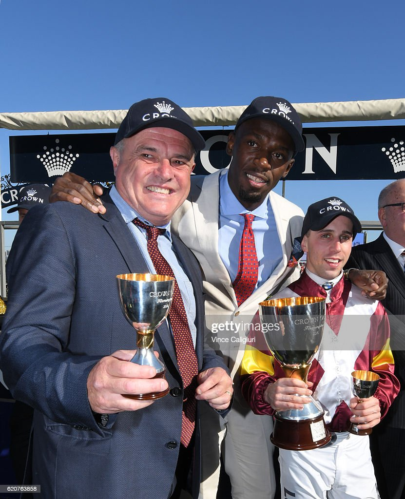 Olympic and world champion sprinter Usain Bolt poses at the trophy presentation with winning jockey Brenton Avdulla and Trainer Lee Curtis after Lasqueti Spirit won Race 8, Crown Oaks on Oaks Day at Flemington Racecourse on November 3, 2016 in Melbourne, Australia.