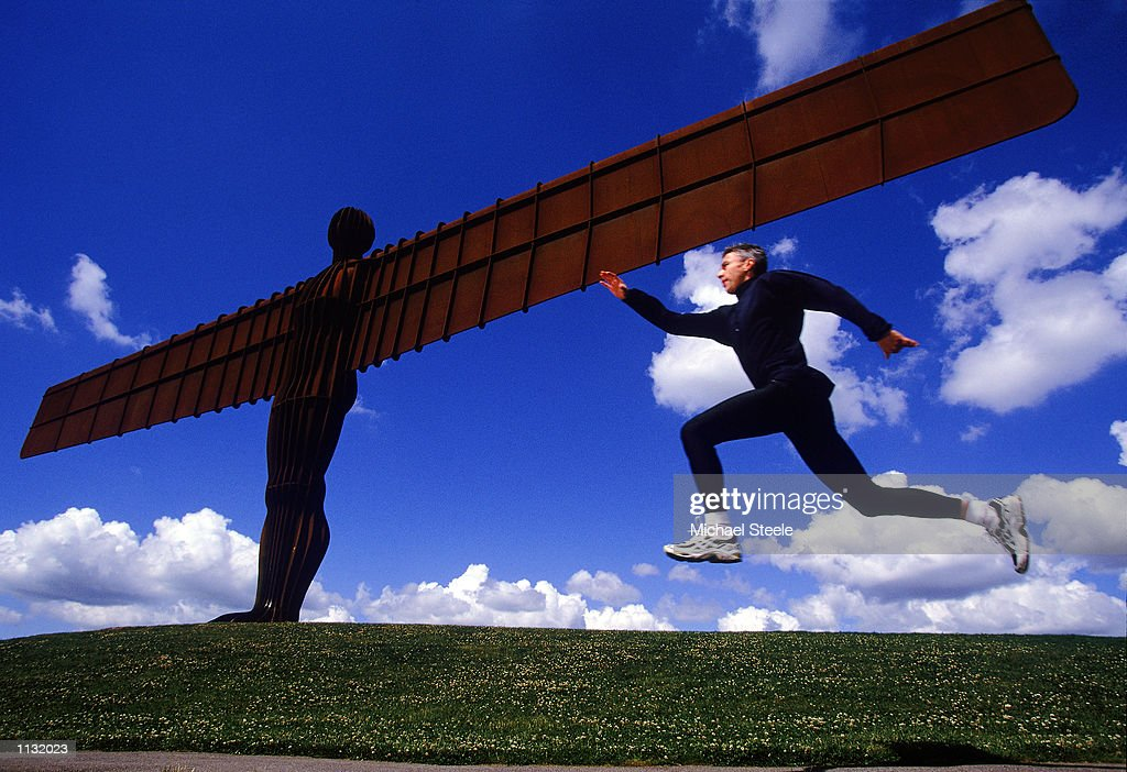 Olympic and World Triple Jump Champion and World Record holder Jonathan Edwards takes a jump at the Angel of the North Sculpture in Gateshead, Great Britain on July 10, 2002. The sculpture was created by internationally renowned sculptor, Antony Gormley, and is situated next to the A1, at Eighton Banks, Gateshead, Tyne & Wear, England.