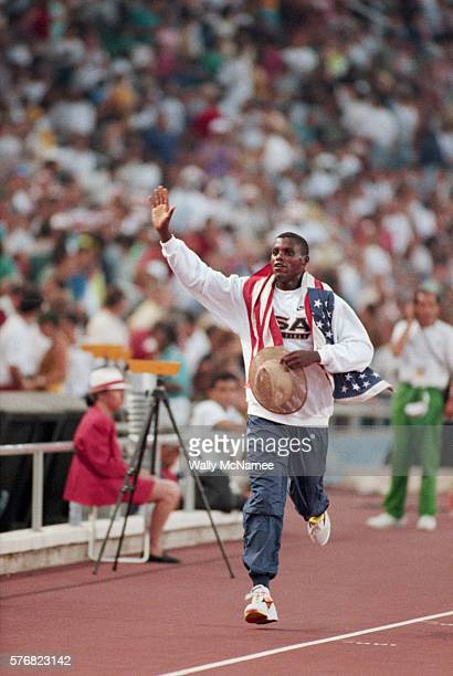 Olympic athlete Carl Lewis carries the United States flag on his shoulders as he runs around the track after winning the gold medal in the long jump...