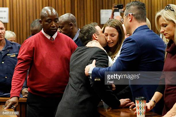 Olympic athlete Oscar Pistorius embraces his sister Aimee Pistorius next to his brother Carl Pistorius as he leaves the High Court after sentencing...