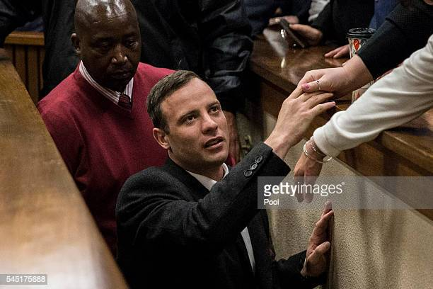 Olympic athlete Oscar Pistorius holds the hand of a relative after sentencing at the High Court on July 6 2016 at the High Court in Pretoria South...
