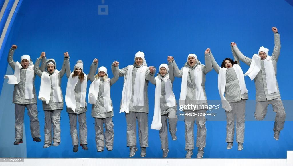 TOPSHOT - Olympic Athletes from Russia who won the silver medal jump on the podium during the medal ceremony for the figure skating team event at the Pyeongchang Medals Plaza during the Pyeongchang 2018 Winter Olympic Games in Pyeongchang on February 12, 2018. / AFP PHOTO / Fabrice COFFRINI
