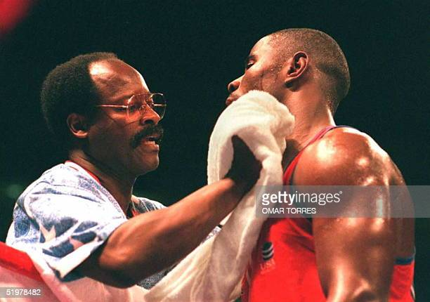 Olympic boxing coach Al Mitchell dries boxer Nate Jones 30 July after he defeated Jiang Tao of China during their 91kg bout at the Alexander Memorial...