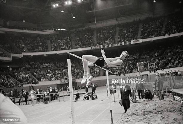 US Olympic Champion high jumper Dick Fosbury of Oregon State appears to be perched on the cross bar as he goes over in his unorthodox backward jump...