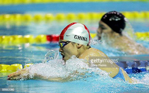 Olympic champion Luo Xuejuan of the Zhejiang Province Swimming Team, competes with Qi Hui of Chinese Army Team during the women's 100 metres...
