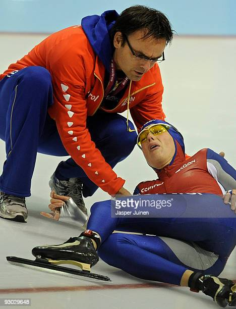 Olympic champion Marianne Timmer is helped by a team member after crashing with Jing Yu of China in the 500m race during the Essent ISU speed skating...