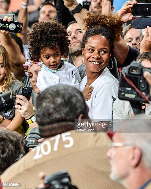 Olympic champion Teddy Riner of France tries hard to get to his son Eden and his partner Luthna Plocus while surrounded by dozens of photographers...