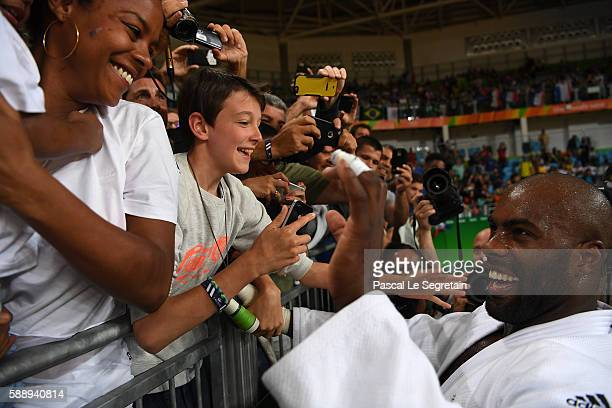 Olympic champion Teddy Riner of France weves to his son Eden and girfriend Luthna Plocus after his Men's 100kg Judo final match on Day 7 of the Rio...