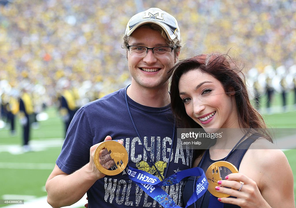 Olympic Champions Charlie White and Meryl Davis show off their Gold Medals during the halftime show at Michigan Stadium during the game between Appalachin State and the Michigan Wolverines on August 30, 2014 in Ann Arbor, Michigan. The Wolverines defeated the Mountaineers 52-14.