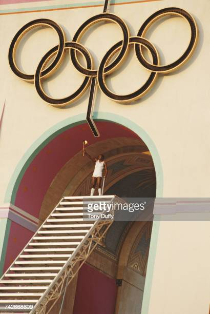 Olympic decathlete gold medallist Rafer Johnson of the United States after climbing the stairs of the Memorial Coliseum prepares to light the Olympic...
