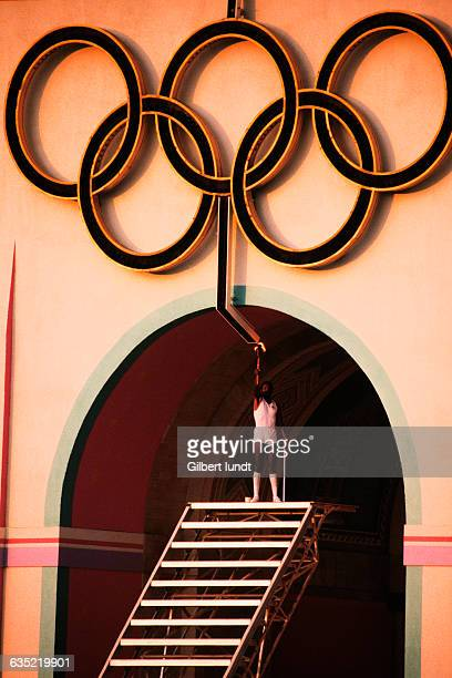 Olympic decathlon gold medal winner Rafer Johnson stands atop a stairway to light the Olympic rings which will in turn light the Olympic Flame at the...