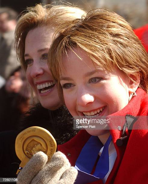 Olympic figure skating gold medalist Sarah Hughes displays her medal with her coach Robin Wagner at a parade in Hughes'' honor March 10 2002 as they...