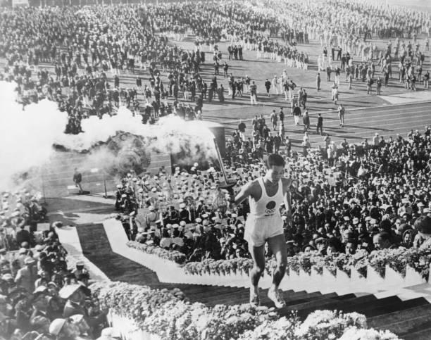 حامل الشعلة الأولمبية يوشينوري ساكاي يصعد الدرج لإضاءة المرجل في افتتاح دورة الألعاب الأولمبية الصيفية في ...