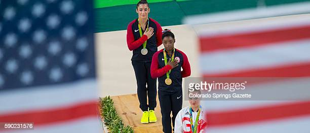 Olympic Floor Exercise gold medalist Simone Biles center with teammate and silver medalist Alexandra Raisman top watch two US flags raised during the...