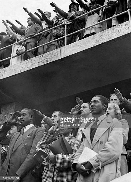 Olympic Games 1936 in Berlin spectators during victory ceremony at Olympiastadion three members of the American team Published by 'BZ' Photographer...