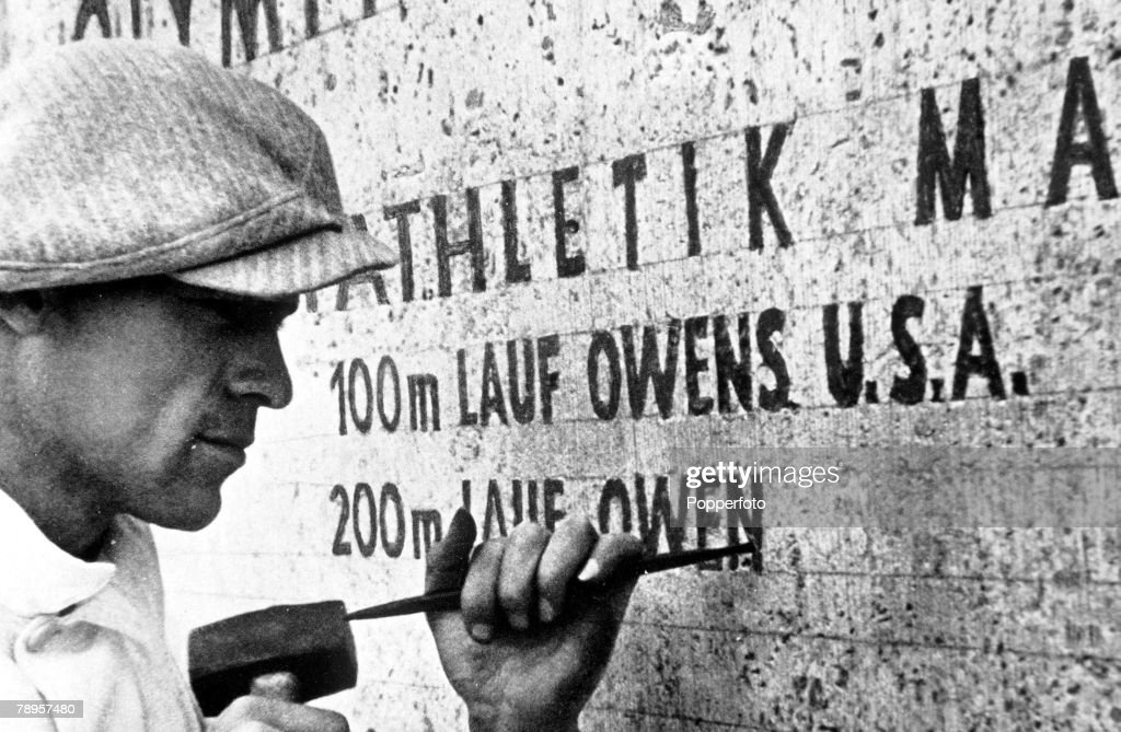 Olympic Games, Berlin, Germany, A stonemason at work records the feat of USA's Jesse Owens, winner of four gold medals in the Games