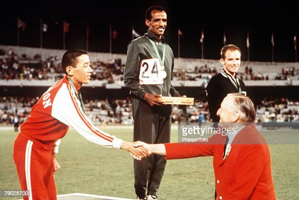 Olympic Games Mexico City Mexico Marathon Ethiopian gold medallist Mamo Wolde stands on the podium with Japanese silver medallist Kenji Kimihara and...
