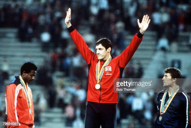 Olympic Games Moscow USSR Men's 100 Metres Great Britain's gold medal winner Alan Wells waves as he stands on the podium with Cuban silver medallist...