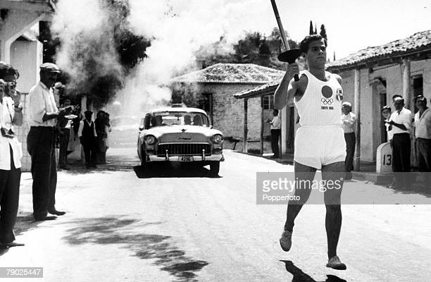 Olympic Games Tokyo Japan A runner holds the Olympic torch as he runs through a Greek village after it had been lit in Olympia