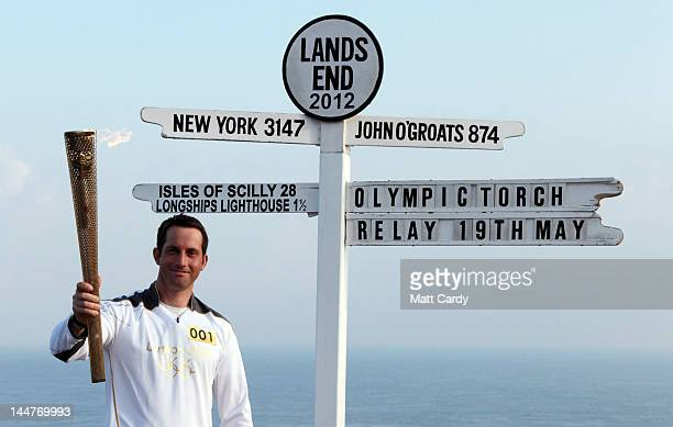 Olympic gold medal sailor and the first London 2012 torchbearer Ben Ainslie poses for a photograph beside the Lands End sign on May 19 2012 in...
