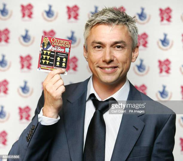 Olympic Gold Medalist Jonathan Edwards holds an Olympic Champions scratchcard at the launch in Piccadilly London