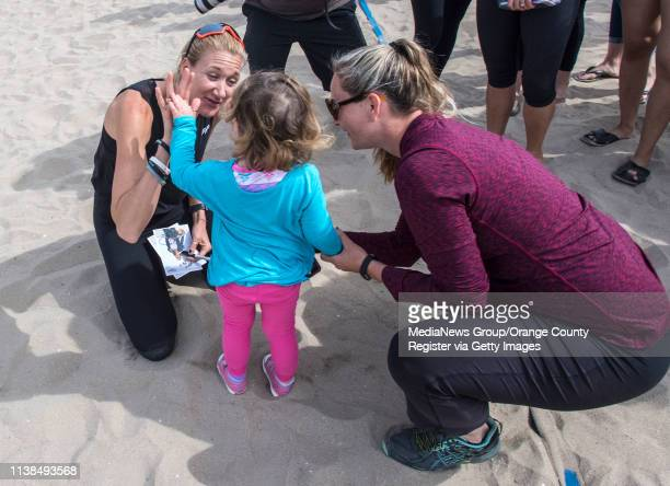 Olympic gold medalist Kerri Walsh Jennings left highfives Savannah Allison of Huntington Beach as her mother Amy Allison right looks on following a...