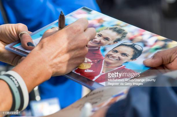 Olympic gold medalist Kerri Walsh Jennings signs a photograph for a volleyball fan following a ceremony in which she and her p1440 program donated 25...